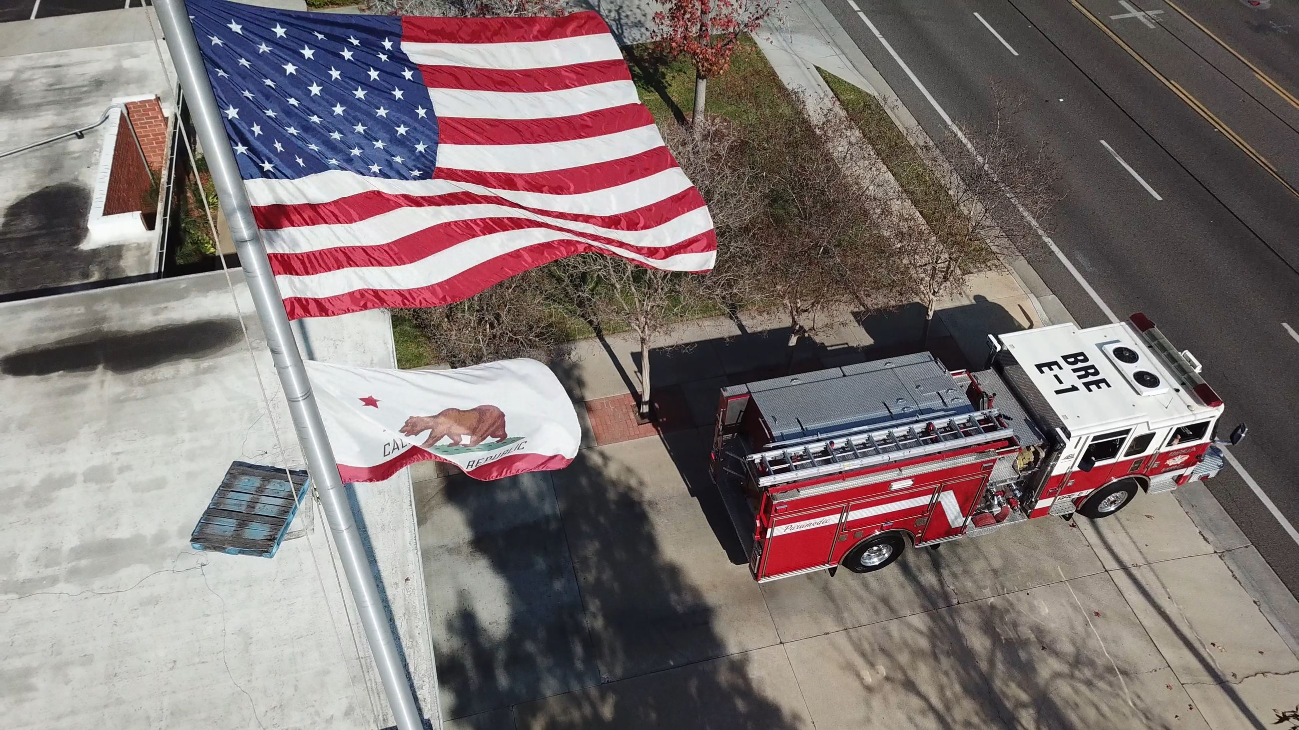 Fire engine rolling out of fire station one with the American Flag waving in the foreground